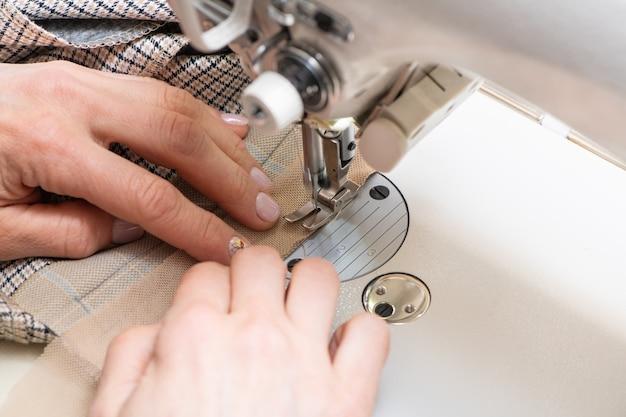 Frauenhand, die weißes tuch durch eine nähmaschine führt. nahaufnahme.