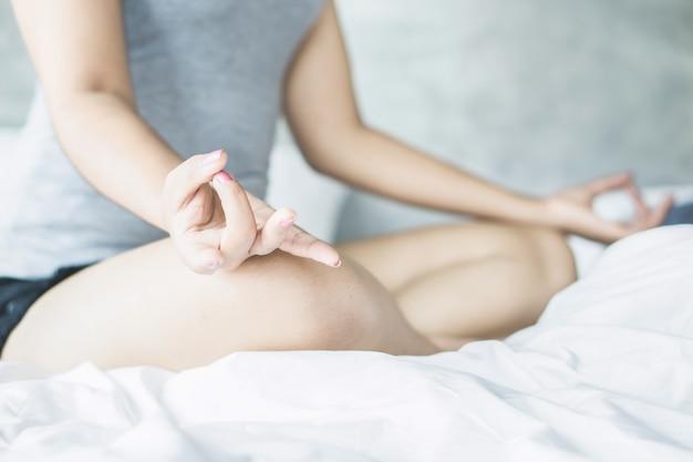 Frauenhand, die yoga tut und auf bett meditiert