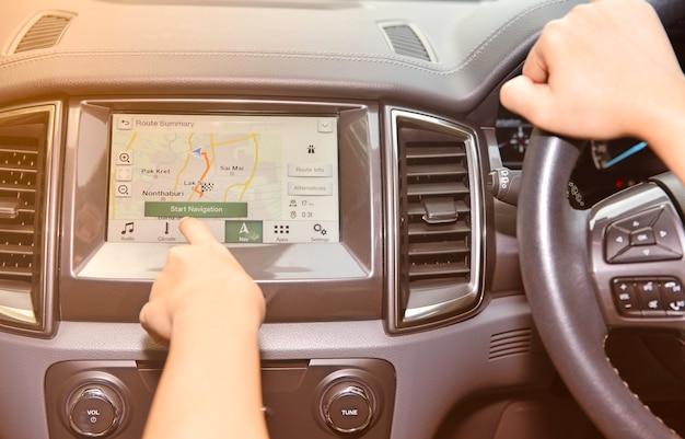 Frauenhand, die zum schirmmultimediasystem mit gps-navigationsanwendung sich berührt.