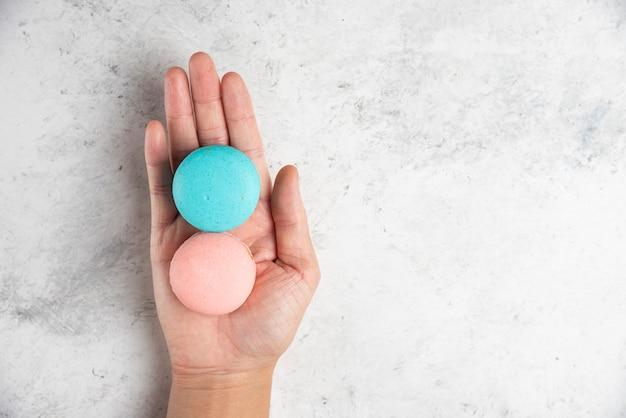 Frauenhand, die zwei leckere macarons auf marmorhintergrund hält.