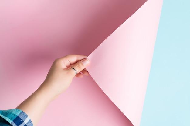 Frauenhand dreht rosa papierblatt auf einem blauen hintergrund mit weichen schatten.