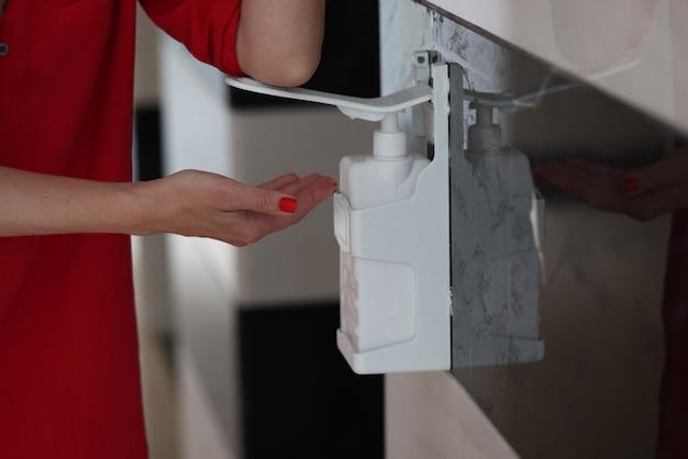 Frauenhand drückt den pumpenkopf auf eine flasche gelseife oder händedesinfektionsmittel und hält geltropfen in der hand