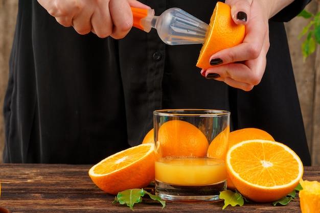 Frauenhand drückt orangensaft nah oben