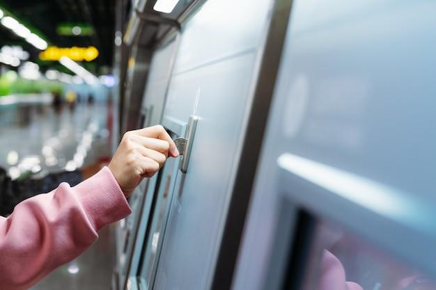 Frauenhand fügt münze ein, um u-bahn-bahnfahrkarte in der maschine zu kaufen.