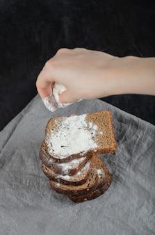 Frauenhand fügt schwarzbrotscheiben mehl hinzu.