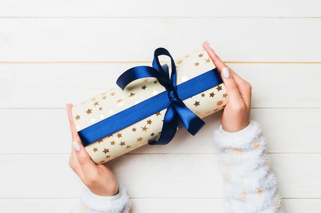 Frauenhand geben valentinsgrußgeschenkbox mit blauem bogen