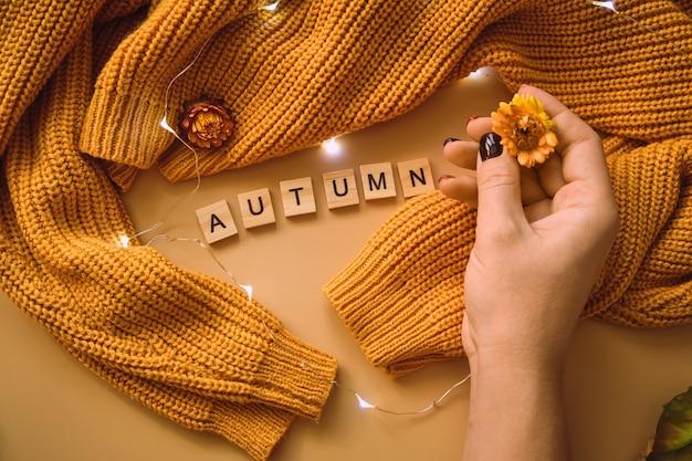 Frauenhand, gelbe ahornblätter und -blumen, glänzende girlande auf einem gestrickten gelben pullover