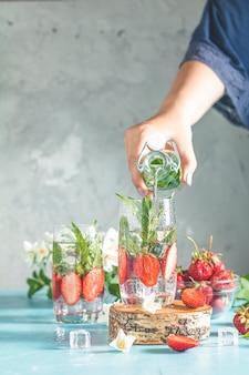 Frauenhand gießt entgiftungswasser von glasflasche zu glas mit erdbeeren, eis und minze. sommerfrischer minz-soda-cocktail, selektiver fokus.