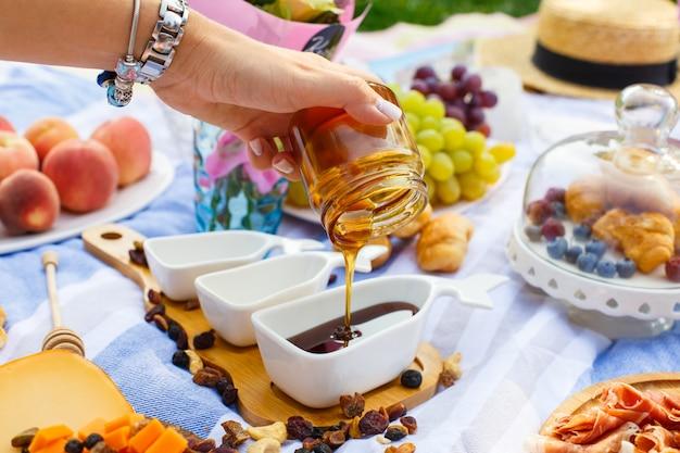 Frauenhand gießt honig von der transparenten flasche zum sauciere