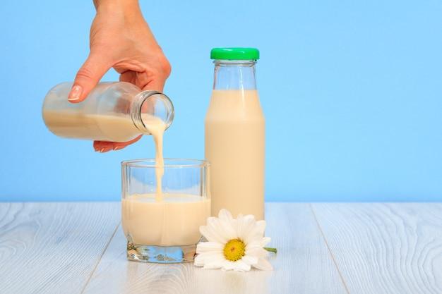 Frauenhand gießt milch in ein glas. flasche frische milch mit kamillenblüte auf blauem hintergrund.