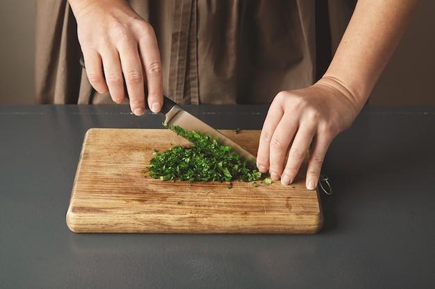 Frauenhand hacken petersilie auf holzbrett auf altem blauem tisch.