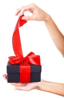 Frauenhand hält band und öffnet geschenkbox isoliert auf weiß