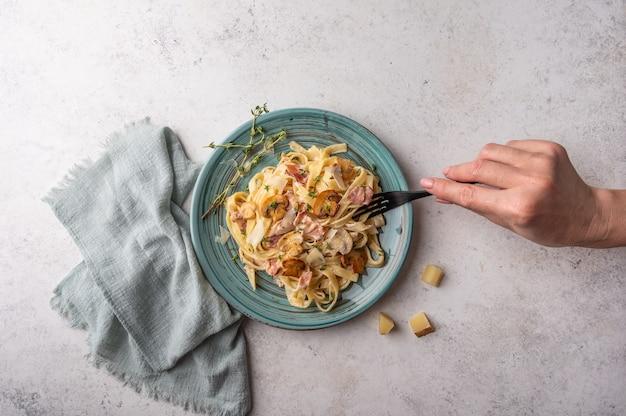 Frauenhand hält eine gabel mit pasta fettuccine mit pilzen, speck, parmesan und bechamel