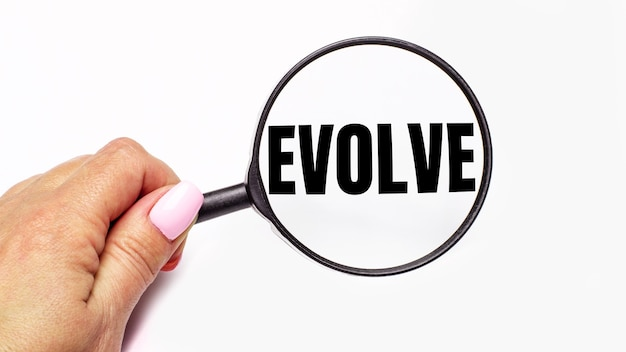 Frauenhand hält eine lupe mit der aufschrift evolve