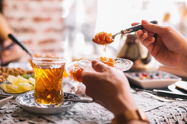 Frauenhand hält einen löffel und einen topf mit quittenmarmelade, die mit tee serviert werden
