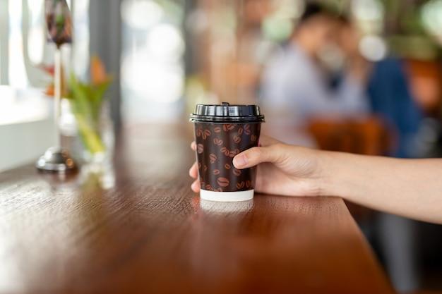 Frauenhand hält einen papiertasse kaffee zum wegnehmen.