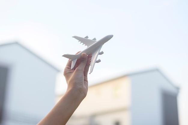 Frauenhand hält flugzeugmodell gegen sonnenuntergang, urlaubsreise, geschäftsschutztransportkonzept.