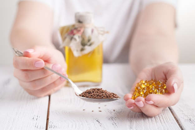 Frauenhand hält gelbe medikamentenkapseln von omega-3-pillen für gesunde nahrungsergänzungsmittel