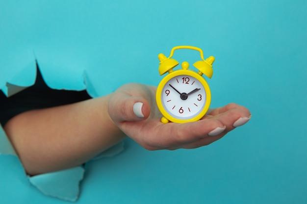 Frauenhand hält gelben wecker durch ein papierloch. zeitmanagement und terminkonzept
