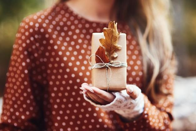 Frauenhand hält geschenk mit herbstlichem blatt