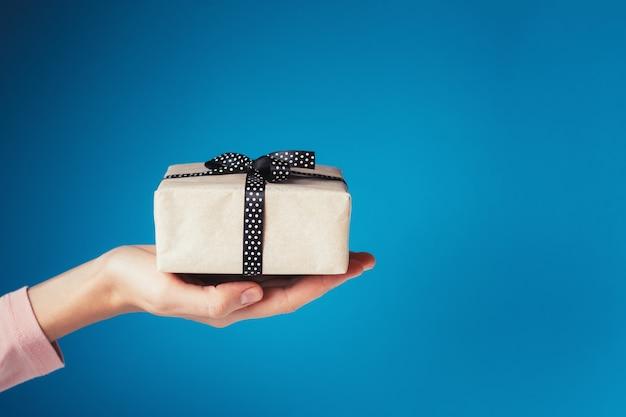 Frauenhand hält geschenkbox auf palme auf blauem hintergrund mit kopienraum