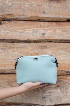 Frauenhand hält handtasche an holzwand