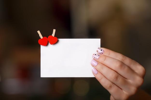 Frauenhand hält papierkarte mit zwei herzstiften. valentinstag-konzept. exemplar für text.