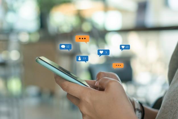 Frauenhand hält smartphone mit likes, follows und kommentarsymbol darüber auf unscharfem hintergrund
