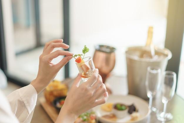 Frauenhand hält verschiedene snacks und vorspeisen essen auf einer cocktailparty.