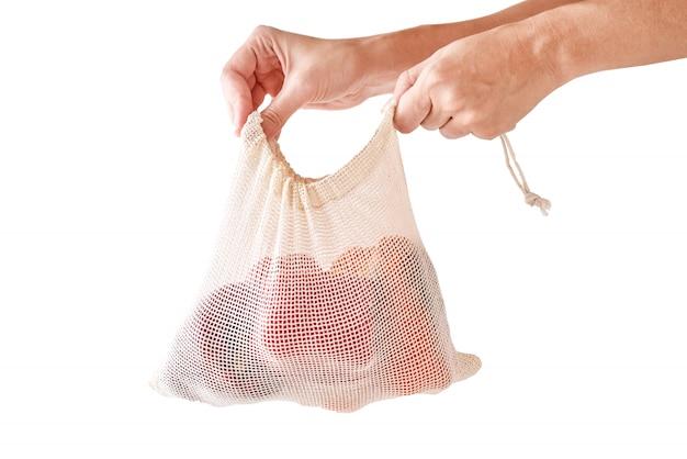 Frauenhand halten frisches bio-gemüse im textilbeutel. null abfall und einkaufskonzept