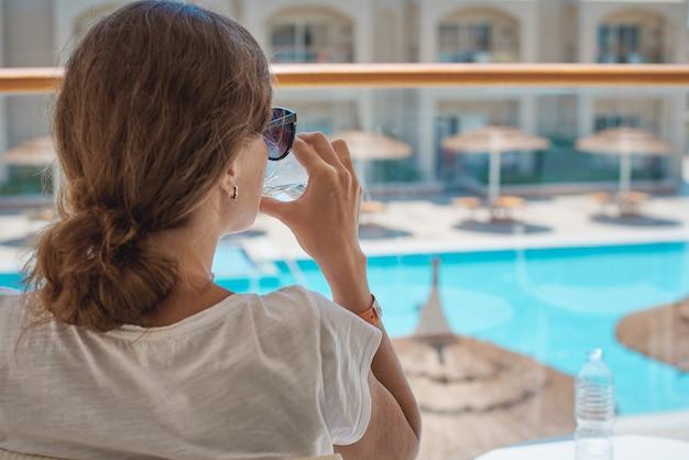 Frauenhand halten glas wasser am hotelbalkon gegen schwimmbad