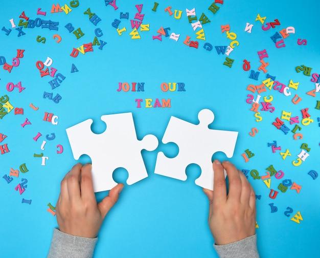 Frauenhand halten große weiße puzzlespiele und die aufschrift verbinden unser team