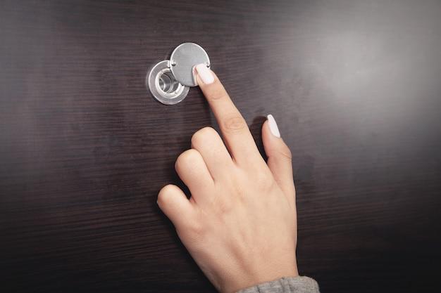 Frauenhand halten guckloch der holztür.