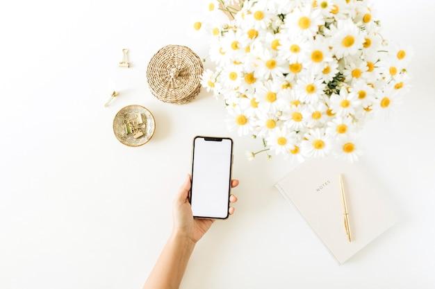 Frauenhand halten smartphone mit leerem bildschirm. home-office-schreibtisch arbeitsbereich mit kamille gänseblümchen blumenstrauß und notizbuch auf weiß