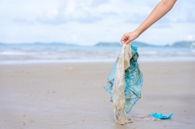 Frauenhand hebt gebrauchte plastiktüte am sandstrand auf