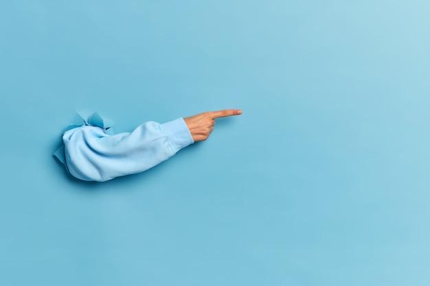 Frauenhand im blauen pullover, der durch papierwand bricht und auf kopierraum zeigt
