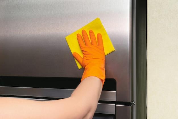 Frauenhand im orange gummi-schutzhandschuh, der grauen silbernen kühlschrank mit gelbem lappen reinigt