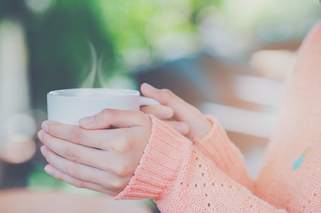 Frauenhand in der warmen strickjacke, die einen tasse kaffee hält.