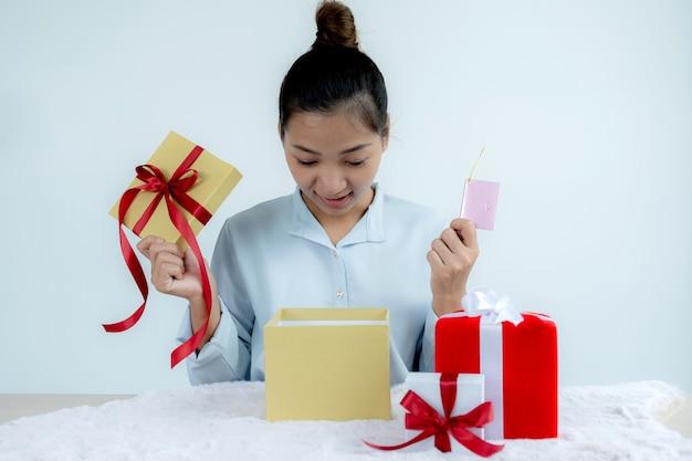 Frauenhand in einem blauen hemd, das eine goldene geschenkbox öffnet, die mit einem roten bandgeschenk für das fest der besonderen feiertage wie weihnachten, valentinstag gebunden gebunden ist.