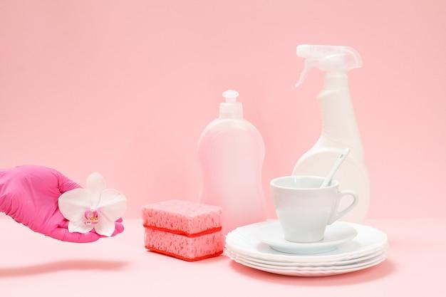 Frauenhand in einem nitrilschutzhandschuh mit orchideenblüte, flaschen mit spülmittel, weißen tellern, einer untertasse, einer tasse auf rosafarbenem hintergrund. wasch- und reinigungskonzept.