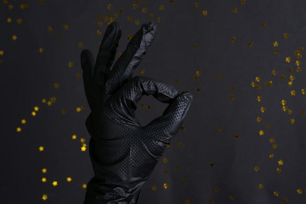 Frauenhand in einem schwarzen latexhandschuh zum reinigen, der ein ok-zeichen auf der gleichen farbe macht.