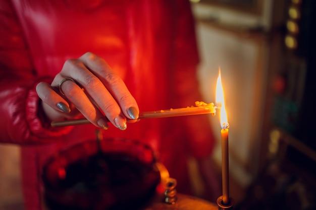 Frauenhand in einer roten jacke setzt eine kirchenkerze.