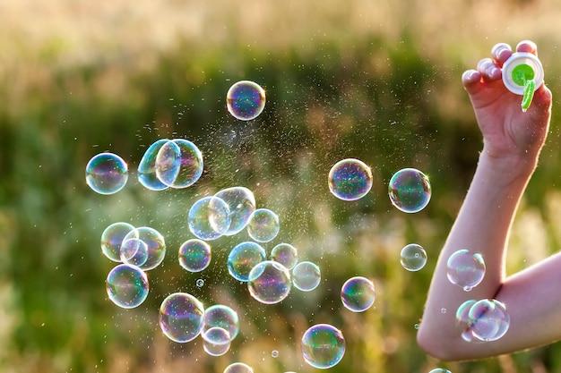 Frauenhand mit blasenden bunten seifenblasen bei sonnenuntergang.
