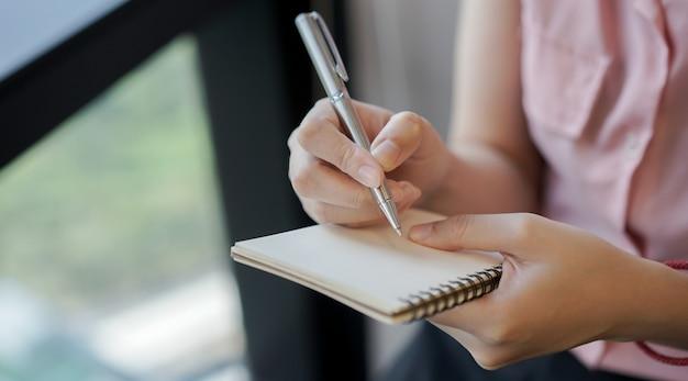 Frauenhand mit bleistift und schreiben auf notizbuch