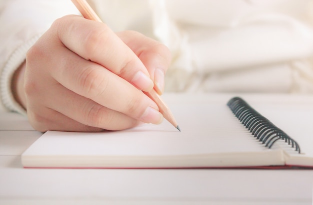 Frauenhand mit bleistiftschreiben auf weißem notizbuch.