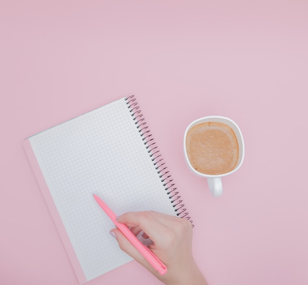 Frauenhand mit dem schreiben auf notizbuchrohling auf dem rosa hintergrund, instagram und geschäftskonzept.
