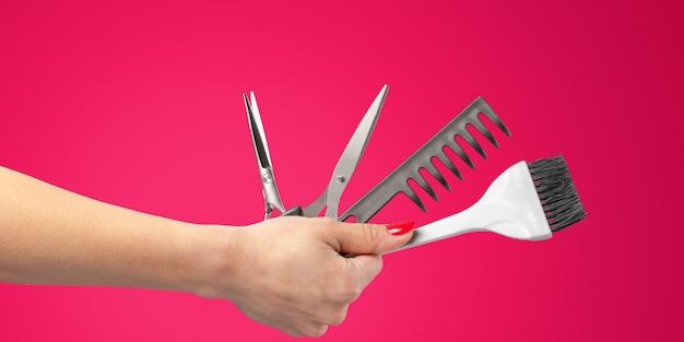 Frauenhand mit den werkzeugen und zubehör eines friseurs lokalisiert