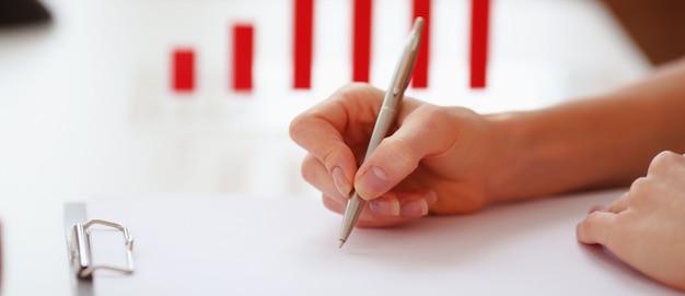 Frauenhand mit einem stift, der auf ein blatt papier schreibt