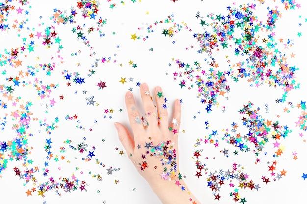 Frauenhand mit festlichen farbsternkonfettis