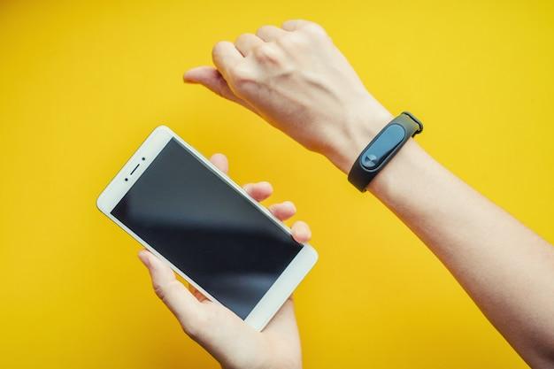Frauenhand mit fitness-tracker und smartphone